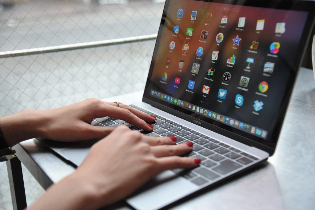 ノートパソコンでクーポンをチェックする赤いマニキュアの手