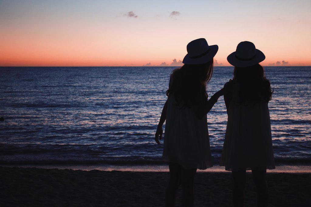 友人と夕日を見る女性