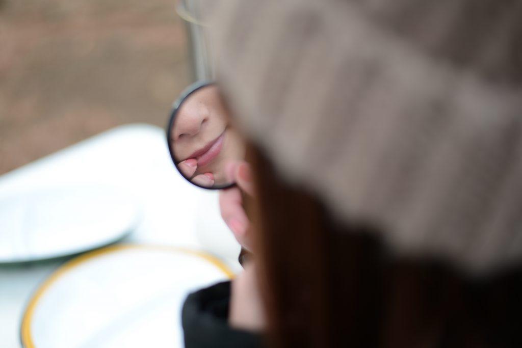 手鏡でチェックする女性