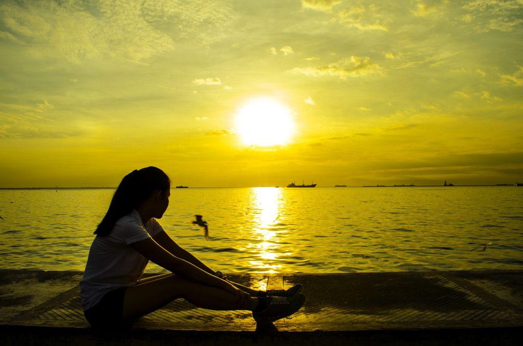 日の入りを眺める女性
