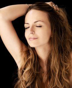 髪の毛をかき上げる女性