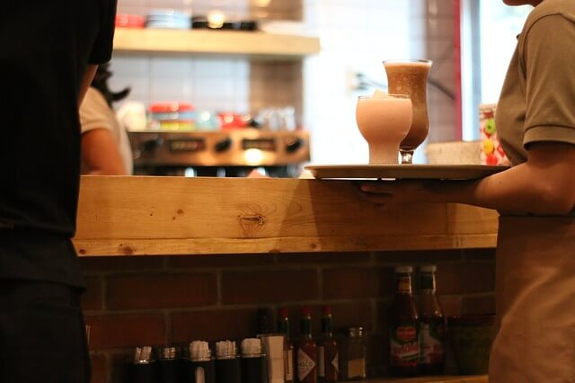 ドリンクを運ぶカフェのウェイター