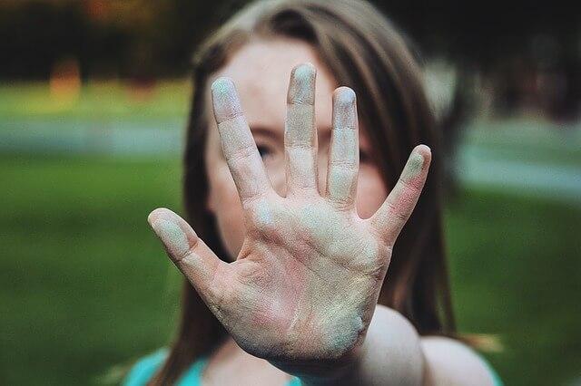手を前に出し拒絶する女性