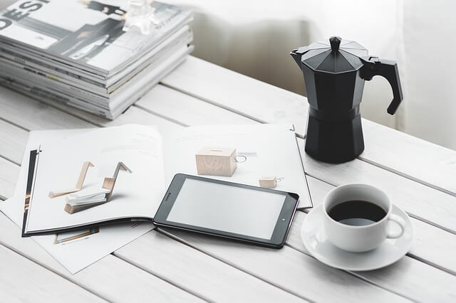コーヒーとタブレットの置かれた仕事場
