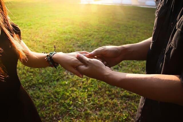 女性の手をつかむ男性