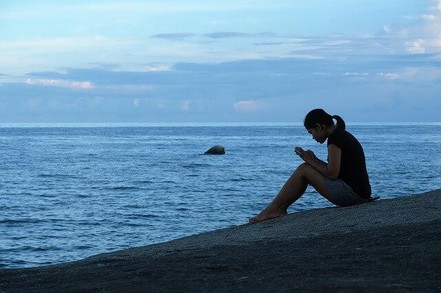 海辺で元彼に復縁メールを送る女性