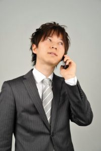 電話で連絡する男性