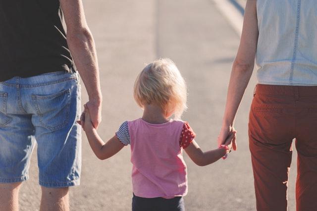 子供と手をつないで歩く夫婦