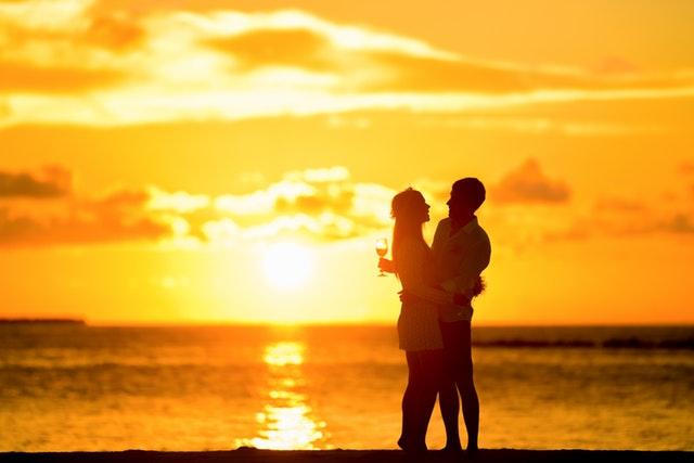夕日をバックに抱き合うカップル