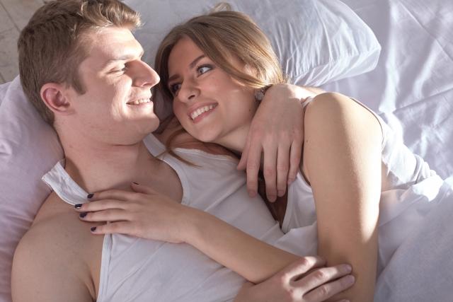ベッドで横になりイチャイチャする男女