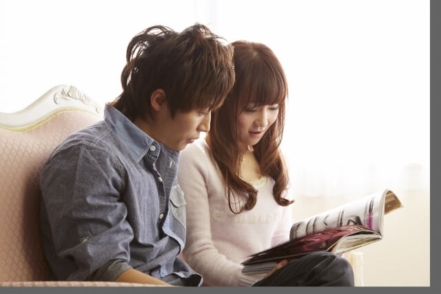 結婚情報誌を眺めるカップル