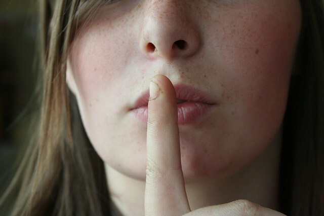 唇の前に人差し指をおく女性