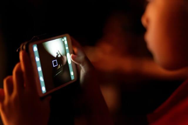 彼の携帯画面を見る女性