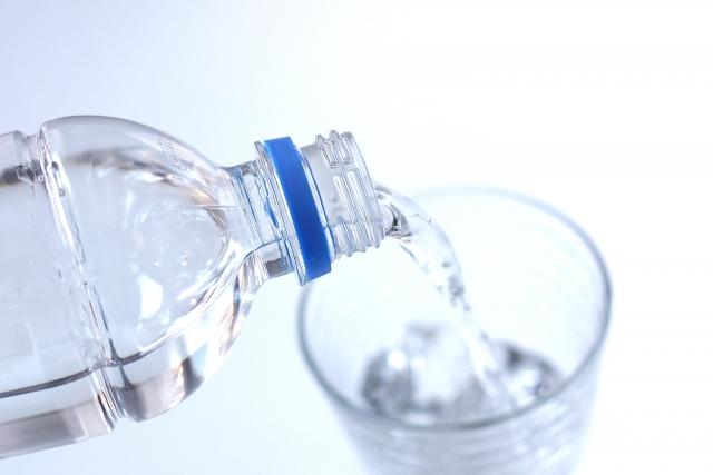 水を飲み口内を潤す女性