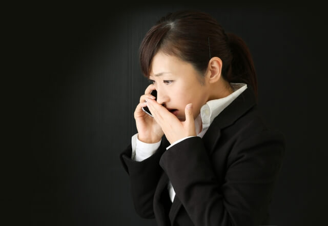 ブライダルフェアに電話する女性
