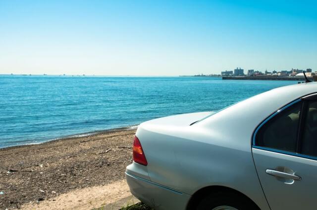 海辺をドライブするカップル