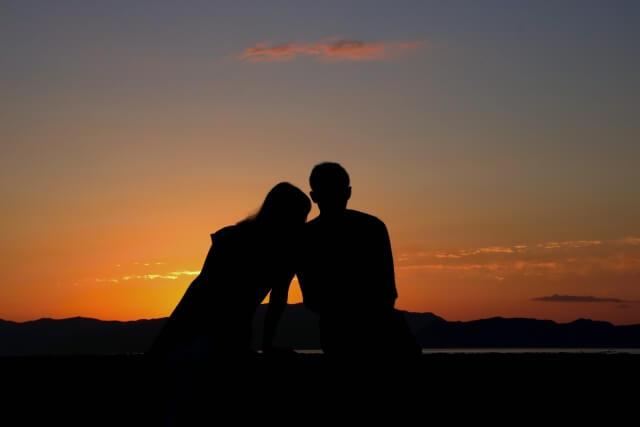 海沿いに腰かけて夕日を見るカップル