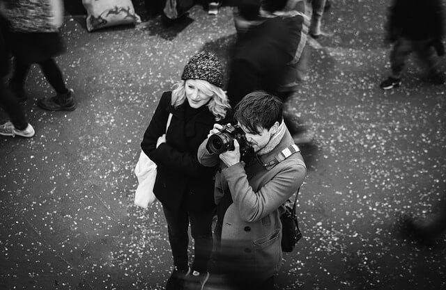 待ちで写真を撮るカップル