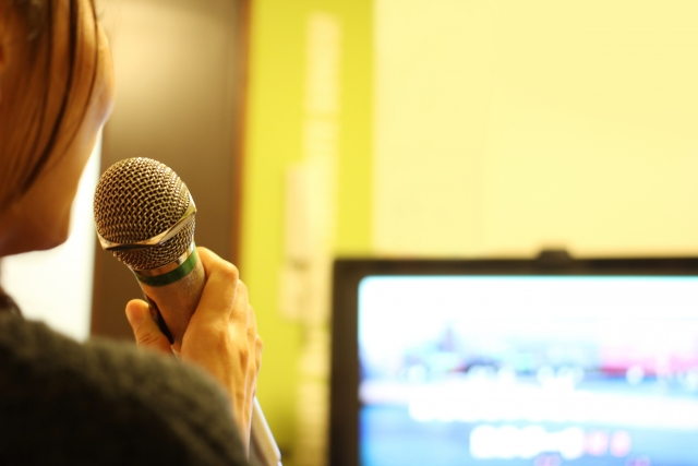 カラオケボックスで歌う女性