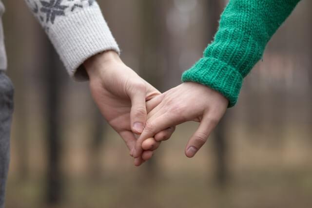 彼と手をつなぐ女性
