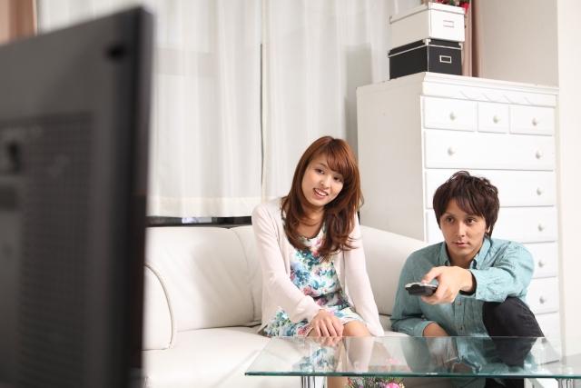 一緒にテレビを見て楽しむ同棲カップル