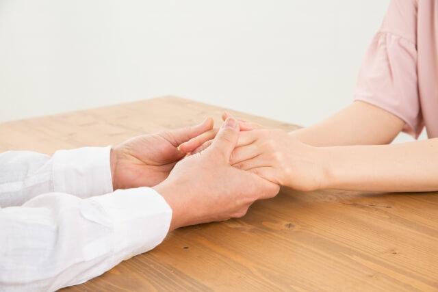 彼の手を握る女性